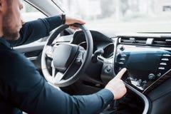 Ufny młody biznesmena obsiadanie przy kołem jego nowy samochód obraz royalty free
