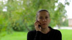 Ufny młody bizneswoman mówi na telefonie w zieleń parku zbiory wideo
