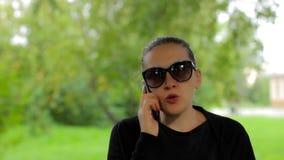 Ufny młody bizneswoman w okularach przeciwsłonecznych mówi na telefonie w zieleń parku zdjęcie wideo