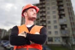 Ufny młody budowniczy pozuje z fałdowymi rękami zdjęcia royalty free