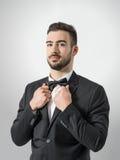 Ufny młody człowiek w smokingu z łęku krawatem pozuje przy kamery mienia kostiumu kołnierzem Fotografia Royalty Free