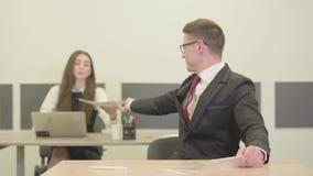 Ufny młody męski kierownik patrzeje w kamerze w kostiumu obsiadaniu przy biurkiem w przedpolu Atrakcyjni potomstwa zbiory wideo