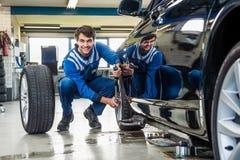 Ufny mechanik Zmienia Samochodową oponę W garażu Obraz Royalty Free