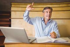 Ufny profesor podnosi jego rękę w sala lekcyjnej obrazy stock
