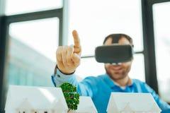 Ufny specjalista wskazuje jego palcowego w górę i jest ubranym rzeczywistość wirtualna szkła zdjęcia royalty free