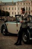 Ufny zamożny młody człowiek z gazetowym pobliskim klasycznym kabrioletem fotografia royalty free