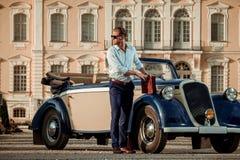 Ufny zamożny młody człowiek z teczką blisko klasycznego kabrioletu zdjęcie royalty free