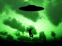 UFO Abduction. Silhouetted UFO that is abducting a human being Stock Illustration