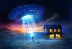 UFO Abduction. A person being abducted in front of his house one spooky evening royalty free illustration