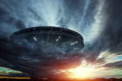 UFO, an alien plate soars in the sky, hovering motionless in the air. Unidentified flying object, alien invasion, extraterrestrial