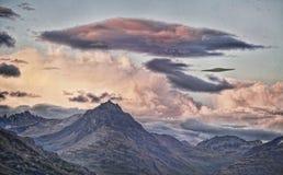 UFO con las montañas púrpuras de la puesta del sol Foto de archivo libre de regalías