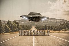 UFO, das über eine leere Wüstenstraße fliegt Stockbild