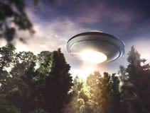 UFO, das über einen Wald fliegt lizenzfreies stockbild