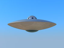 UFO flying in blue sky Stock Photo