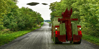 Ufo flying over a country road Stock Images