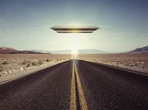 Ufo flying over an empty desert road Royalty Free Stock Photo