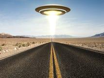 Ufo flying over an empty desert road Stock Photo