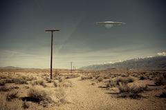 UFO over desert road. Low flying UFO spaceship hovering over a desert dirt road near a telephone pole with a vintage look Stock Photography