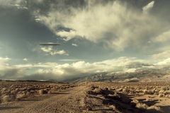 UFO over desert road. UFO spaceship hovering over a desert road with puffy clouds processed with a vintage look Royalty Free Stock Photo