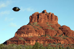 UFO's do exhist here is proof #2. A silver metalic looking UFO hovers around bell rock in Sedona Arizona against a blue sky royalty free stock photos