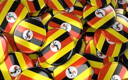 Uganda förser med märke bakgrund - högen av ugandiska flaggaknappar Arkivbilder