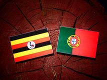 Uganda flag with Portuguese flag on a tree stump isolated. Uganda flag with Portuguese flag on a tree stump vector illustration