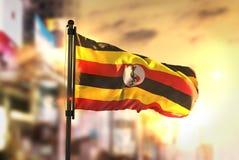 Uganda flagga mot suddig bakgrund för stad på soluppgångpanelljuset arkivfoton