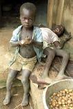 Ugandan aardappels van de jongensschil door gehandicapte broer royalty-vrije stock afbeelding