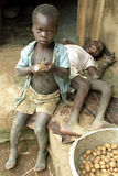 Ugandan boy peeling potatoes by disabled brother