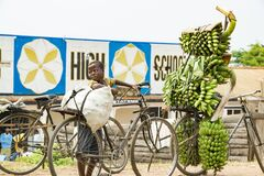 Boy with heavy load on his bike in Uganda. Boy carrying loads on bike. Bicycles loaded with plantains, cooking bananas and bags
