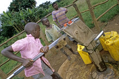 Ugandan Children fetch water at water pump. Uganda, Luweero district, village Zirobwe Bungo: group portrait of Ugandan kids, boys and girl, who fetch water from royalty free stock image