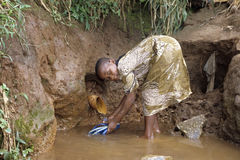 Ugandan Girl cleaning thongs in well Stock Images