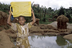 Ugandan Girl at well carrying drinking water. Uganda, capital, city Kampala, a child is at a pit of water, groundwater in a suburb of Kampala. She wears a heavy Royalty Free Stock Photo