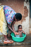 Ugandan mother bathing her child Stock Photos