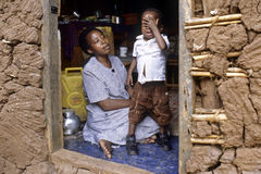 Ugandan Mother and child in homely atmosphere. Uganda, capital, city Kampala: in the slum Mulago-Kiwonvu is a woman sitting in the doorway of her house carefully Stock Image