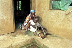 Ugandan mother takes care of son with disabilities. Uganda, Luweero district, village Kalasa: a woman takes loving care of her physically and mentally disabled Royalty Free Stock Photography