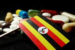 Ugandisk flagga med lotten av medicinska preventivpillerar som isoleras på svart backgro Royaltyfria Bilder