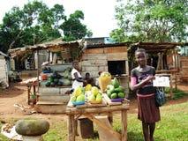 Ugandiska kvinnor som säljer lokal frukt på vägsida Arkivfoto