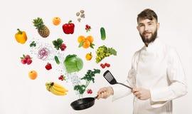 uggling与菜和其他食物的制服的英俊的专业厨师在厨房里 厨师和飞行蔬菜和水果 免版税库存照片