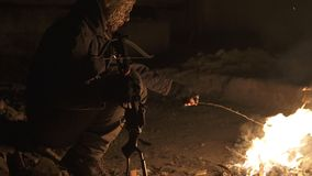 Ugly Dangerous zombie monster Sitting near the bonfire with heavy Cross bow in Dark ruined concrete shelter. Horror. Character concept, Armed and grasepainted stock video