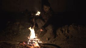 Ugly Dangerous zombie monster Sitting near the bonfire with heavy Cross bow in Dark ruined concrete shelter. Horror