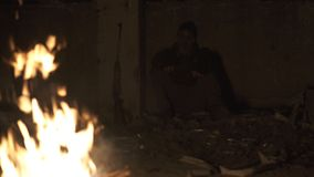 Ugly Dangerous zombie monster Sitting near the bonfire with rifle in Dark ruined concrete shelter. Horror Character. Concept, Armed and grasepainted entity. 4k stock video