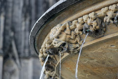 Ugly demon statue with streaming water from mouth near Cologne c Royalty Free Stock Images