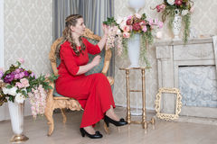 Ugly domineering woman is posing in red dress Royalty Free Stock Photo