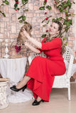 Ugly domineering woman is posing in red dress Stock Photos