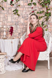 Ugly domineering woman is posing in red dress Stock Photography