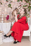 Ugly domineering woman is posing in red dress. In studio stock photos