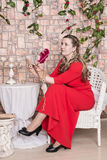 Ugly domineering woman is posing in red dress. In studio royalty free stock images