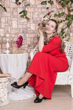Ugly domineering woman is posing in red dress. In studio stock images