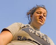 Ugly Face. Teenager making ugly face against blue sky outdoors Stock Images